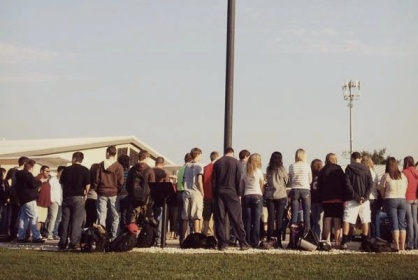 High schoolers praying around a flagpole.